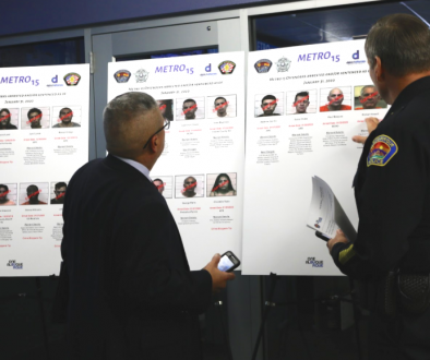 "police officials inspect a ""Metro 15"" poster of most wanted criminals"