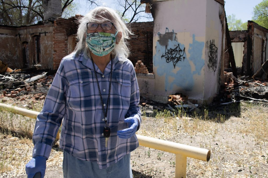 native american woman in facemask in front of childhood home