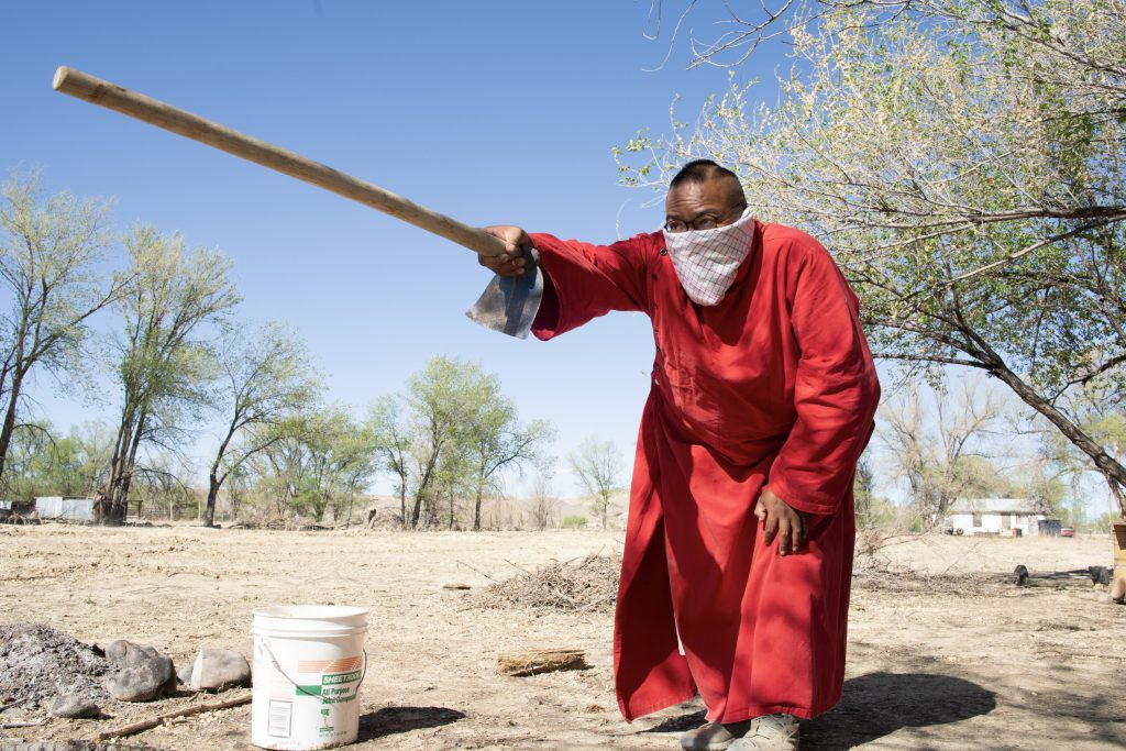 native american man in red robe points with hoe to a planting site
