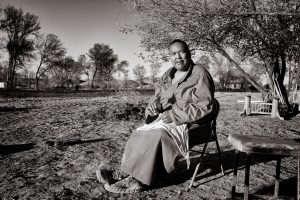 Native american man rests in chair in field