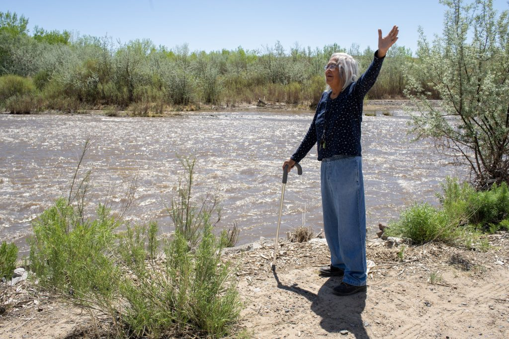 native american woman next to river with outstretched hand
