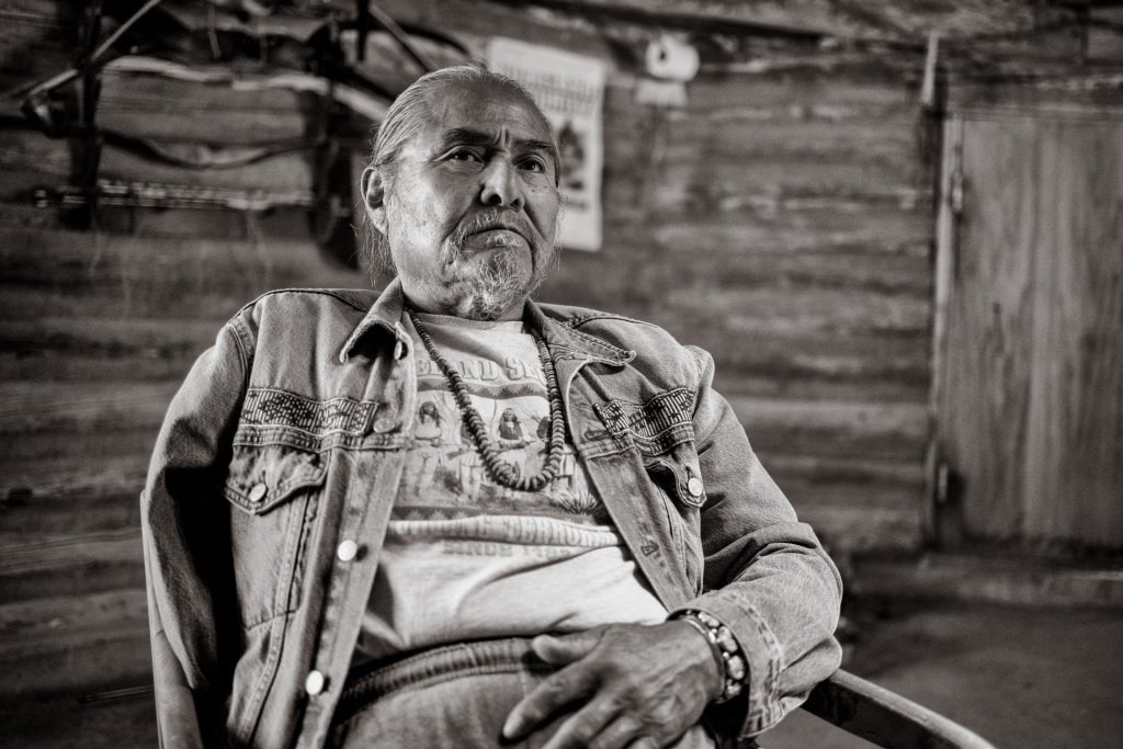 native american man with one arm leans back in chair