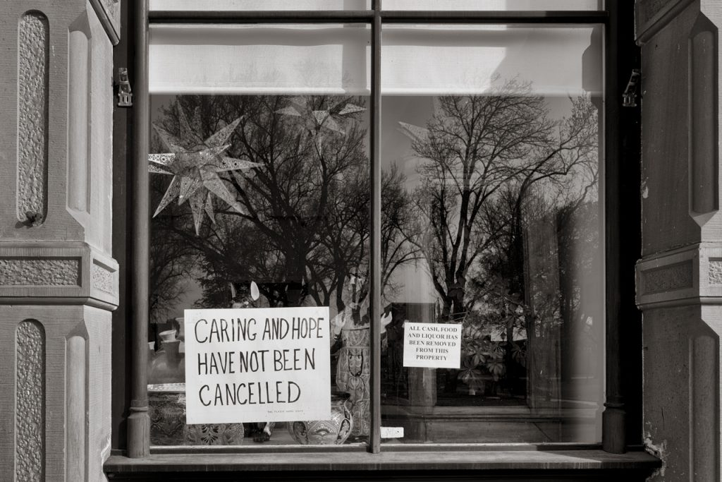 """store front sign saying """"caring and hope have not been canceled"""""""