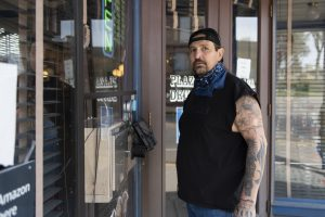 man with tattooed arms at front door of shop