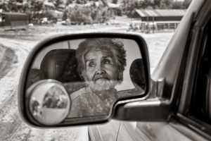 reflection of elderly woman in car mirror