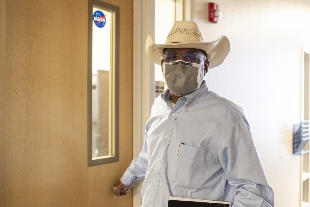 man with cowboy hat and face mask