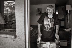 man with walker at door to motel room