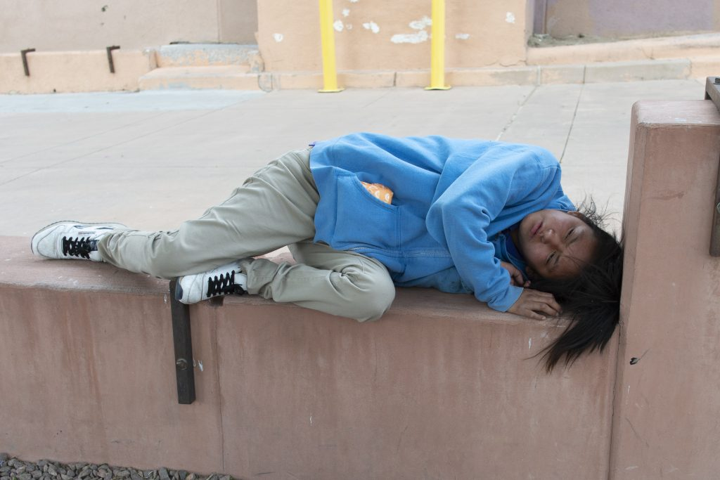 woman asleep on an outdoor concrete wall