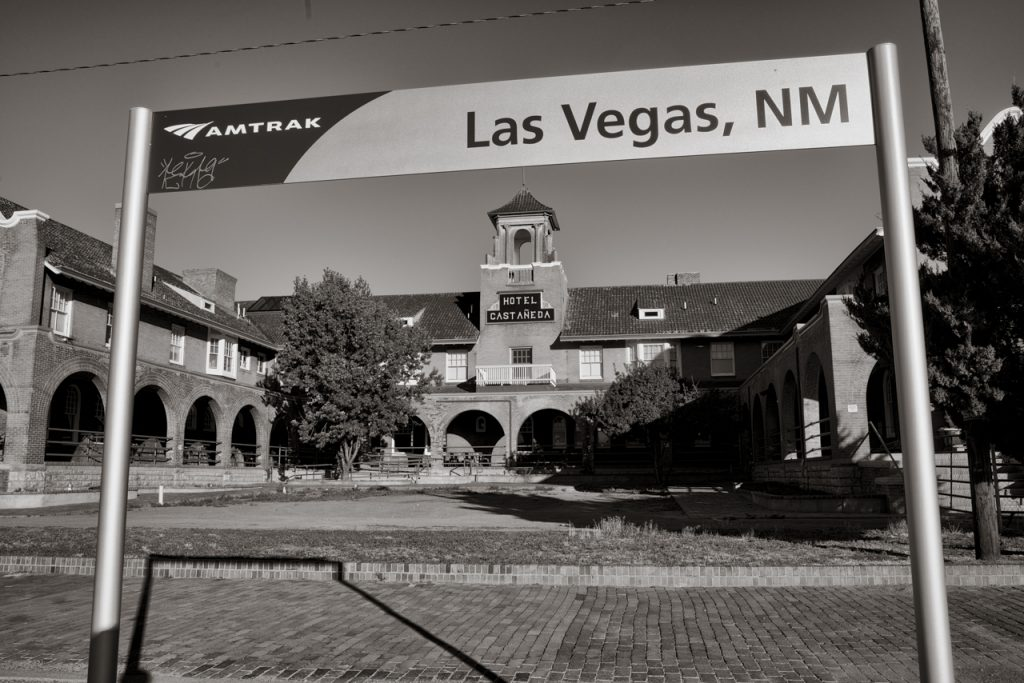 hotel visible behind Amtrak station sign for Las Vegas, NM