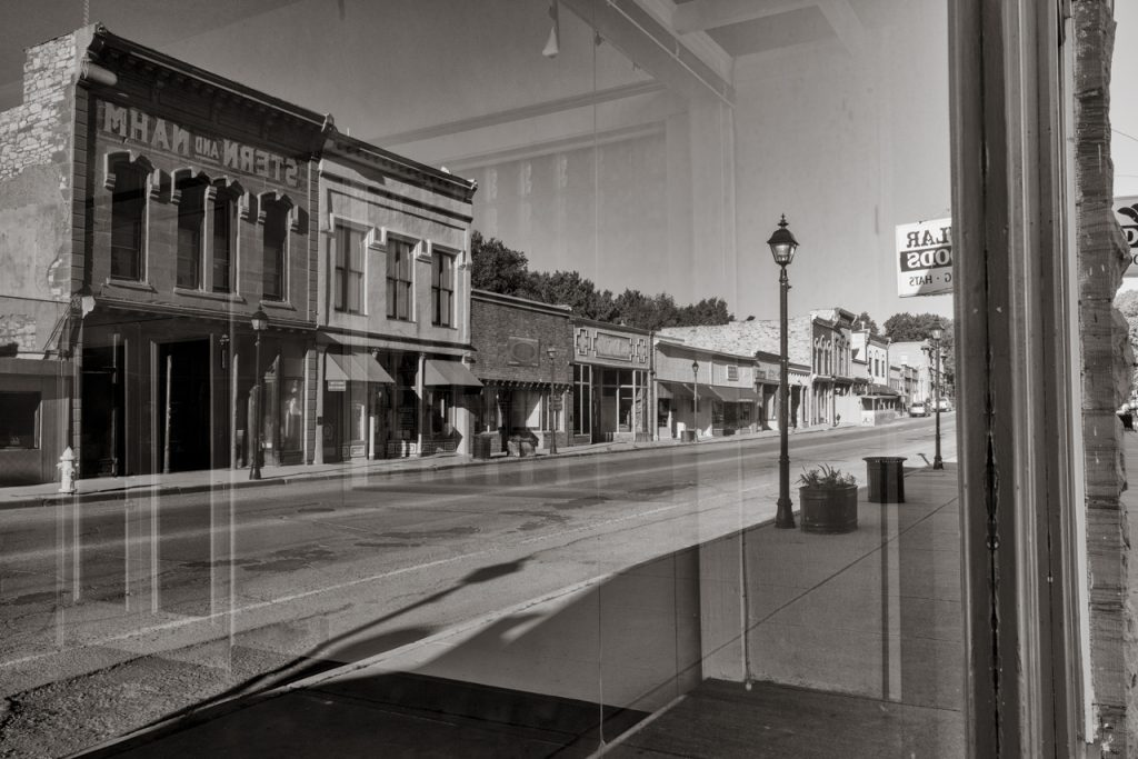 view of deserted town street from inside window