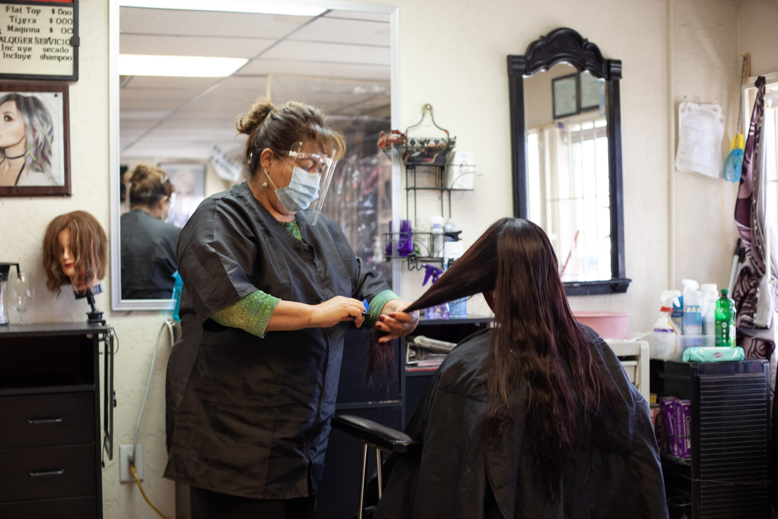 stylist cuts woman's hair in salon