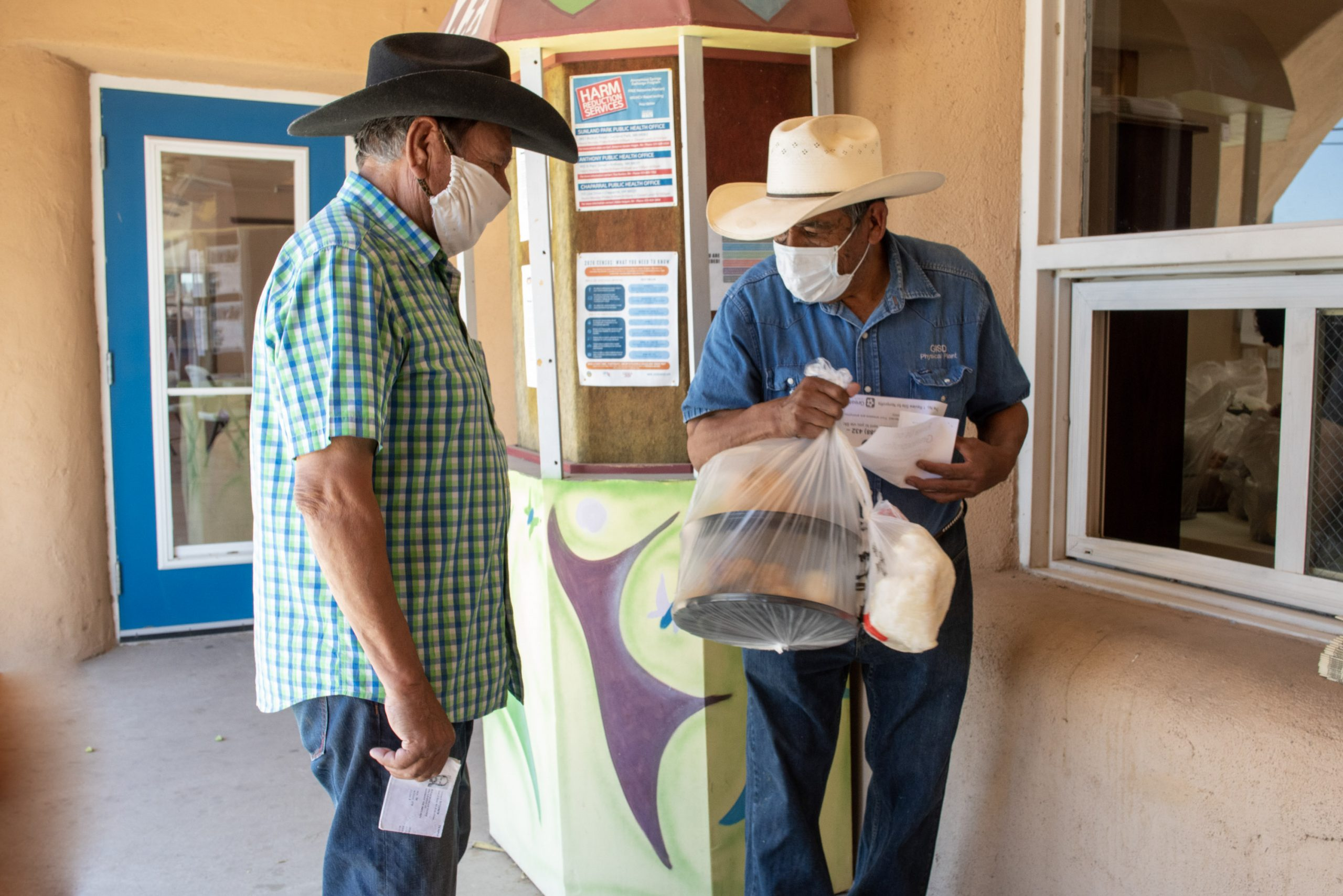 two men in cowboy hats hold with food bags