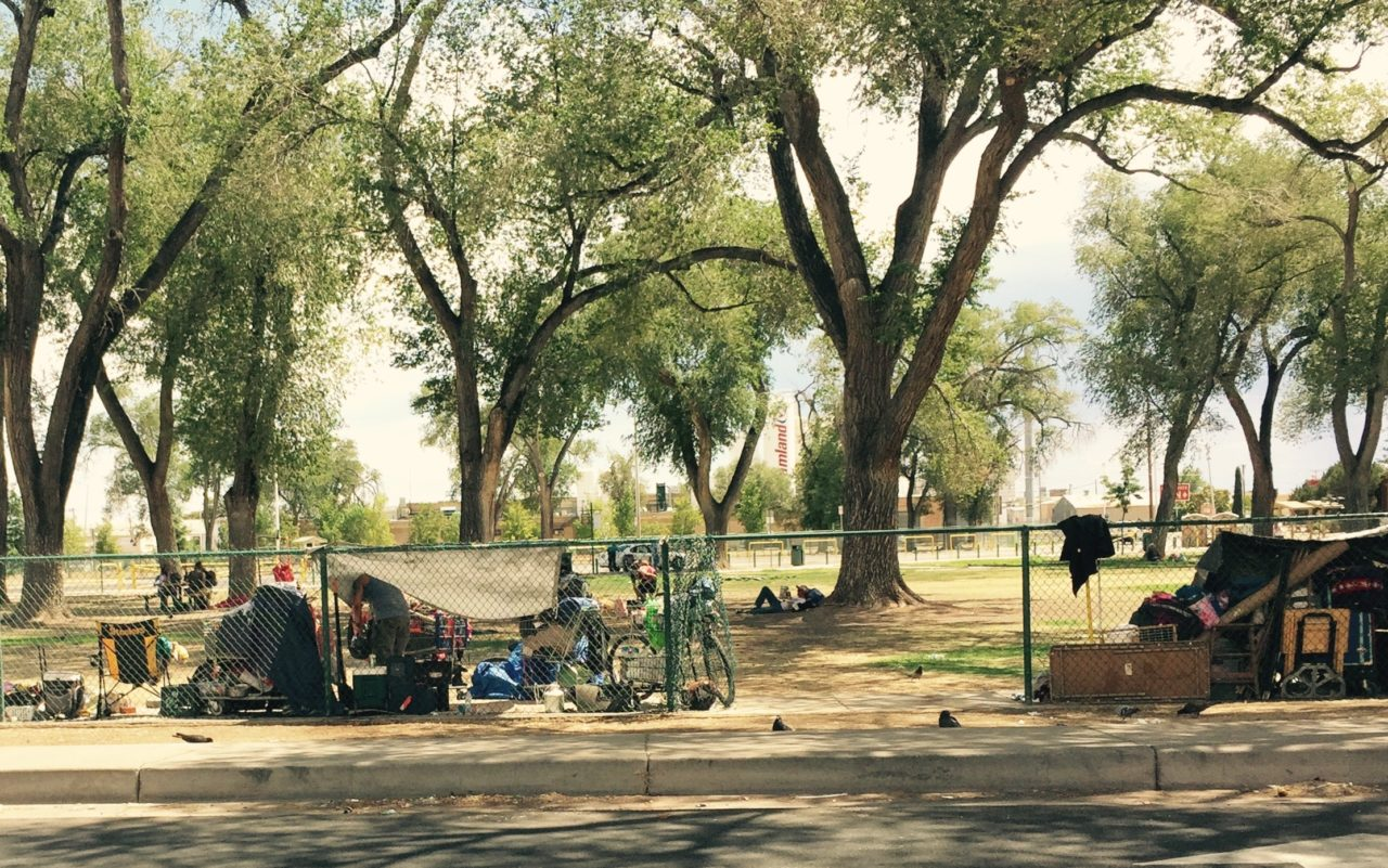 people and tents behind a fence in a city park