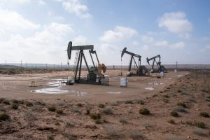 three pump jacks in desert setting